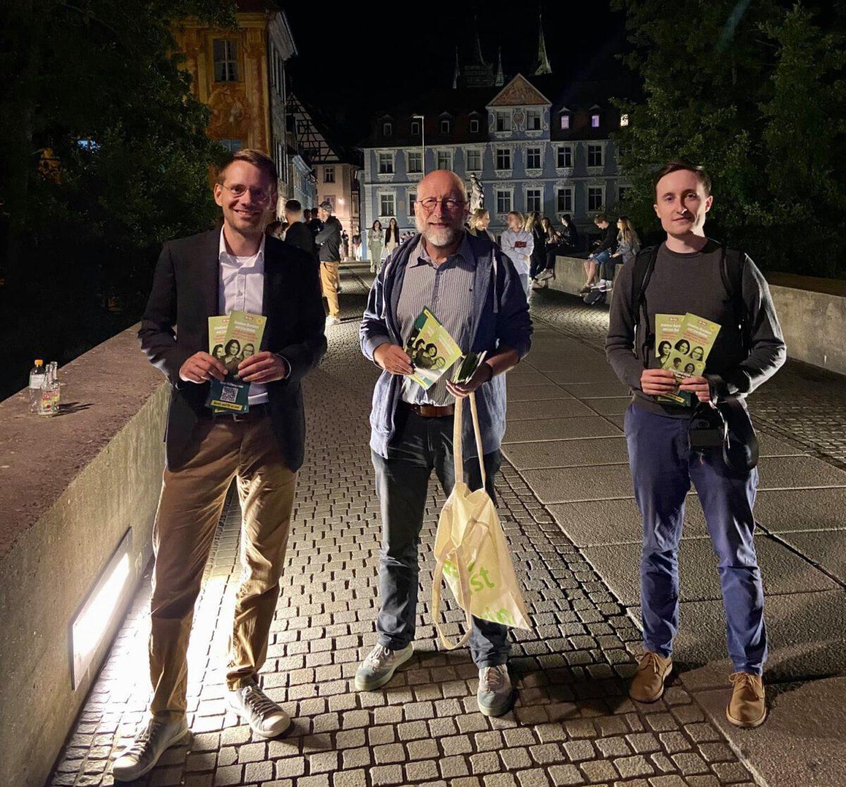 Thomas von Sarnowski mit zwei grünen Mitgliedern auf einer Brücke bei Nacht mit Flyern in der Hand